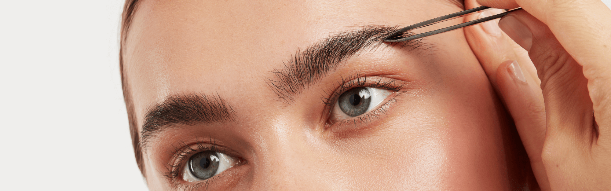women plucking brows with eyeko tweezers