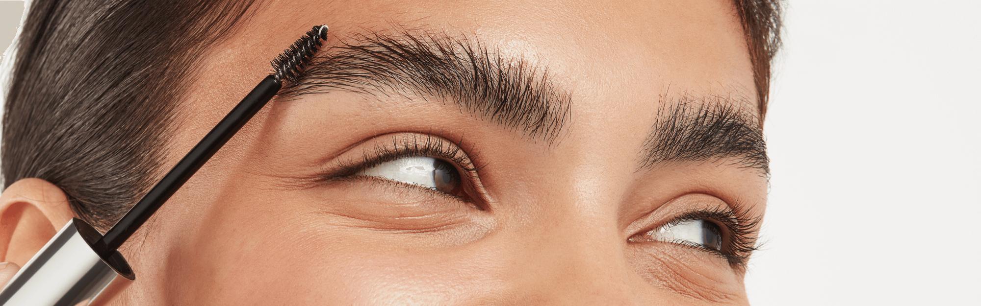 women applying clear brow gel