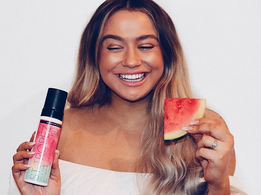 St.Tropez customer smiling, showing off her natural looking tan. She has a real slice of watermelon in her left hand and in her right hand is the St.Tropez Self Tan Watermelon Infusion Bronzing Mousse product.