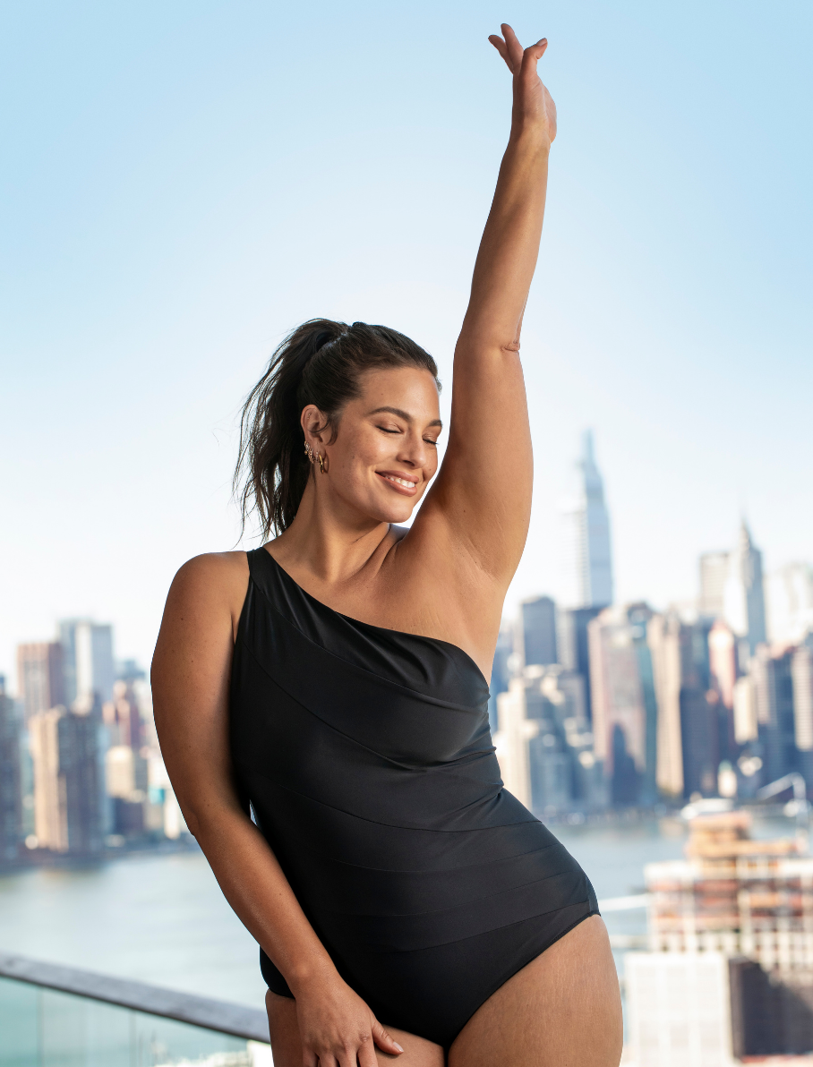 Ashley Graham in black swimsuit with one arm raised smiling.