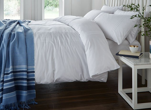 Hit snooze - White bed with blue cover at the end