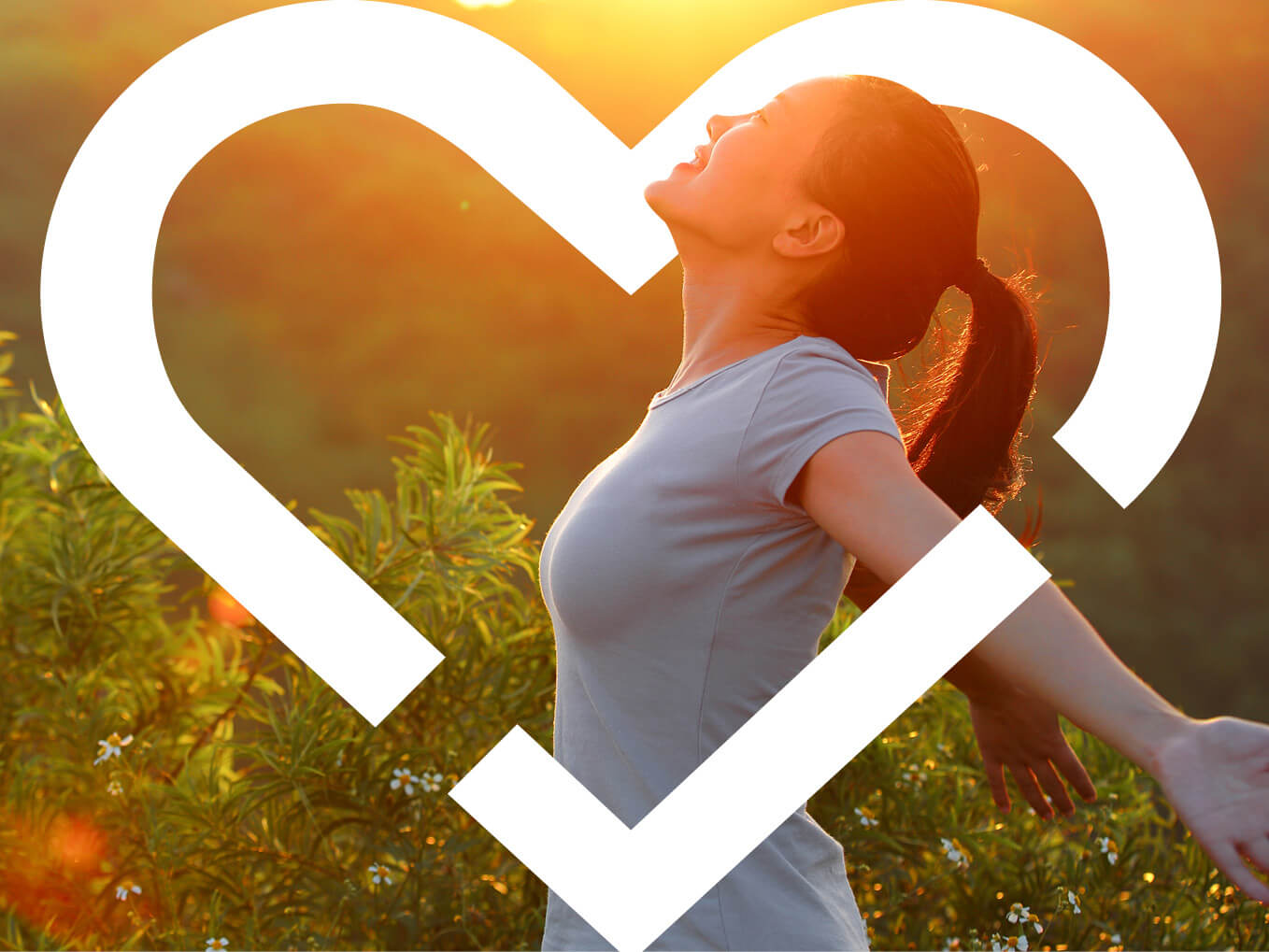 Individual smiling and posing with a sunset backdrop, surrounded by heart logo
