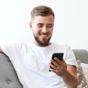 Man smiling at his phone after receiving an email from Your Coca-Cola
