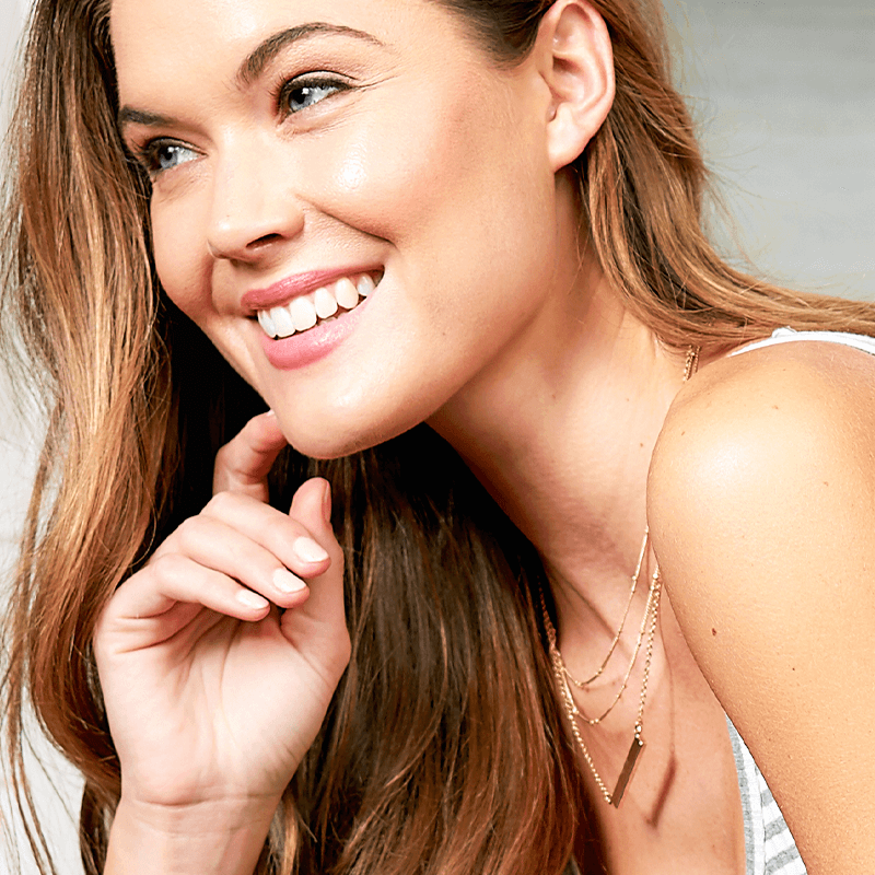 women smiling with her hand on her face